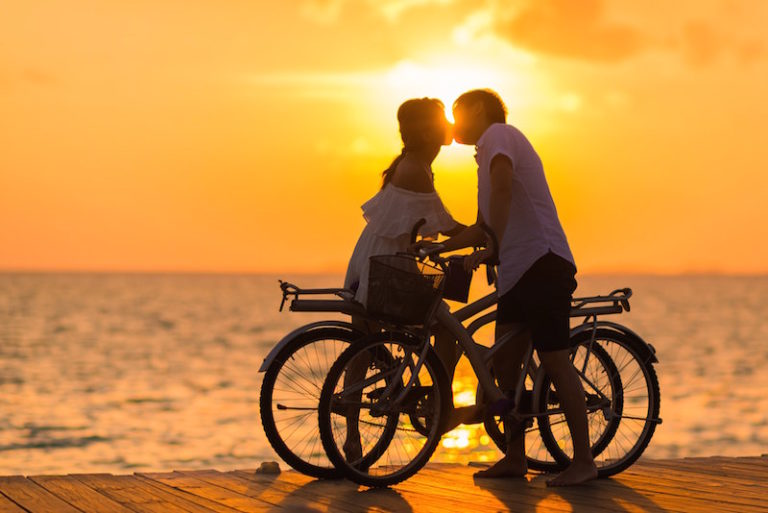 anniversary cover man and woman kissing over bikes