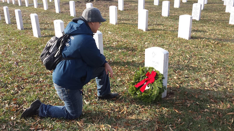 kneeling at my grandfathers grave after laying wreath